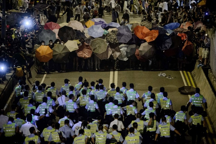 Image: Police forces march toward pro-democracy protesters during a standoff outside the central government offices in Hong Kong