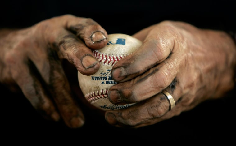 Image: Baltimore Orioles clubhouse worker Sammy Sanchez rubs mud on a new baseball in 2009