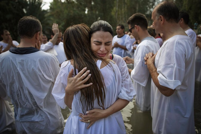 Image: Christian pilgrims from Brazil embrace after they are baptized near the northern Israeli city of Tiberias