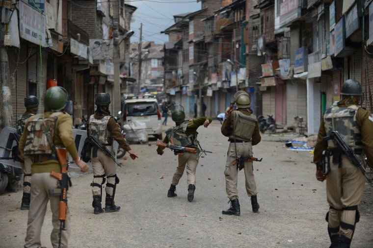 Indian police throw stones during clashes with flood-affected Kashmiri residents protesting against the state government in Srinagar on Oct. 15.
