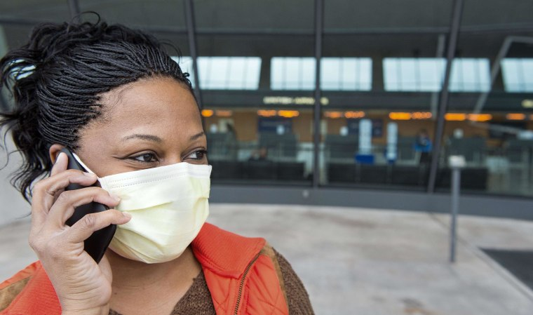 Image: A nurse arriving from Dayton, Ohio, and concerned about Ebola reports, wears a precautionary surgical mask at Dulles International Airport