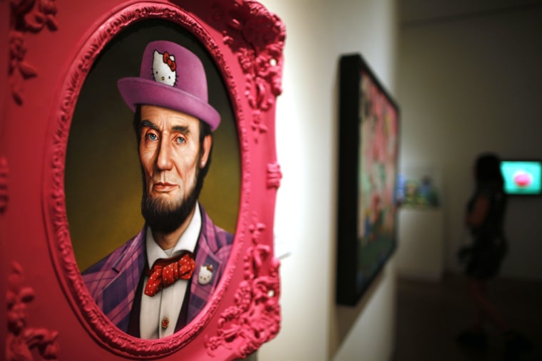 Image: A painting titled 'Hello Lincoln' by Scott Scheidly hangs at the 'Hello! Exploring the Supercute World of Hello Kitty' museum exhibit in honor of Hello Kitty's 40th anniversary, at the Japanese American National Museum in Los Angeles