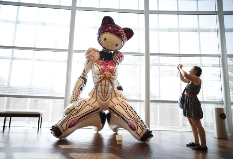 Image: A woman photographs 'Super Space Titan Kitty' by Colin Christian at the 'Hello! Exploring the Supercute World of Hello Kitty' museum exhibit in honor of Hello Kitty's 40th anniversary, at the Japanese American National Museum in Los Angeles