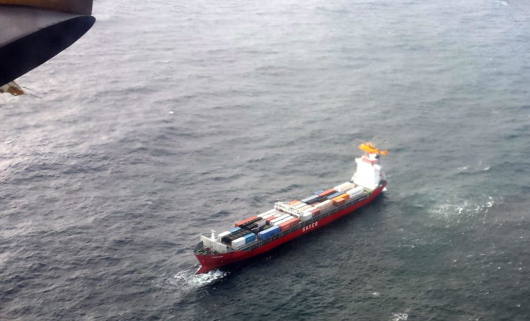 Image: A Canadian Coast Guard helicopter flies near a Russian container ship, carrying hundreds of tons of fuel drifting without power in rough seas off British Columbia's northern coast