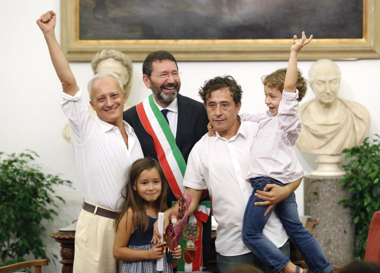 Image: A gay couple, officially married outside Italy, pose with Rome's mayor Marino during a ceremony for the registration of their marriage in Rome