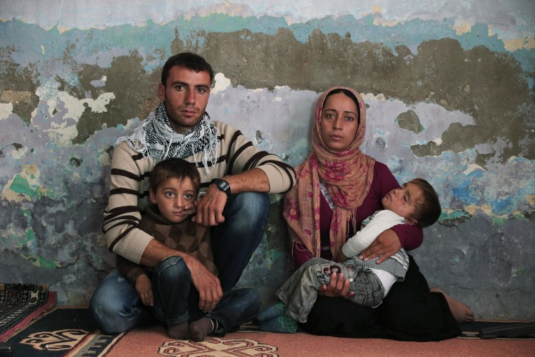 Syrian Kurdish fighter Delkhwaz Sheikh Ahmad, 22, sits with his wife Siham, 23, and their two sons, Dilyar, left, 3 and Ibrahim, 2, right, at his brother's house in Suruc, on the Turkey-Syria border, as he prepares to leave for Kobani, Syria, to rejoin the fighting, Friday, Oct. 17, 2014.