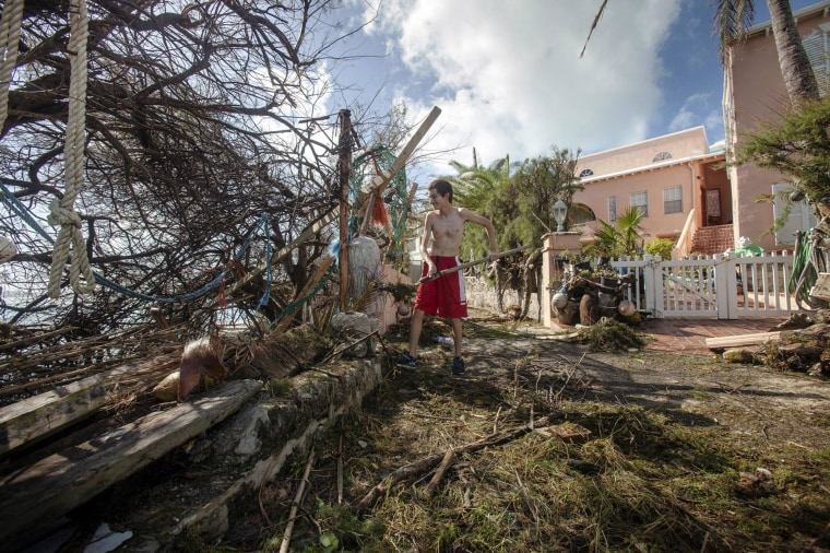 Image: Stefano Ausenda shovels debris away from his driveway after Hurricane Gonzalo passed through in Sandys Parish