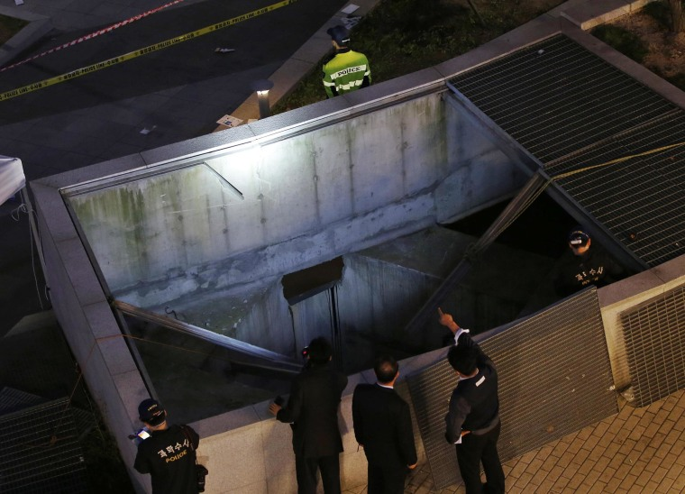 Image: Police officials examine the scene of an accident at a shopping district in Seongnam