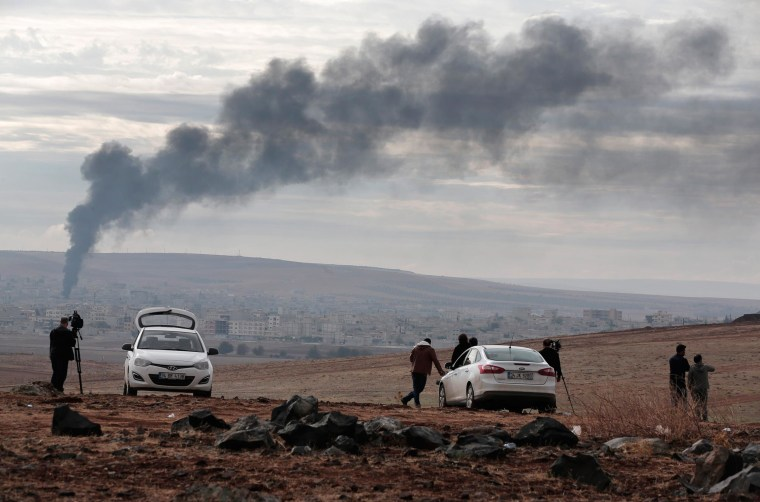 Image: Members of the media on a hilltop on the outskirts of Suruc, at the Turkey-Syria border, watch as smoke from a fire rises following a strike in Kobani, Syria