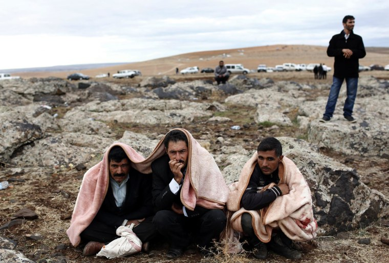 Image: People watch from a hill after a US-led coalition airstrike on Kobani, Syria, took place.