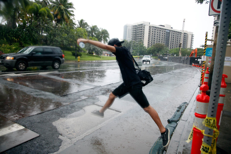 Image: A man jumps over a puddle as he prepares to board a bus in Honolulu on Sunday.