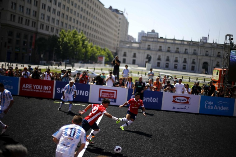 Chilean players and Argentinian players fight for the ball during 12th Homeless World Cup soccer tournament in front of the government palace in Santiago October 19, 2014. Some 52 teams, including 12 women teams, take part in the tournament, which starts on Sunday until October 26th. Participants of the tournament are either asylum seekers, homeless or in drug or alcohol rehabilitation treatment. REUTERS/Ivan Alvarado (CHILE - Tags: SPORT SOCCER SOCIETY DRUGS POVERTY)
