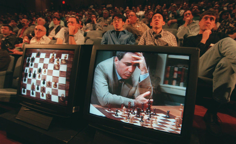 Image: An audience watches as Garry Kasparov is shown on a television screen contemplating his next move against Deep Blue