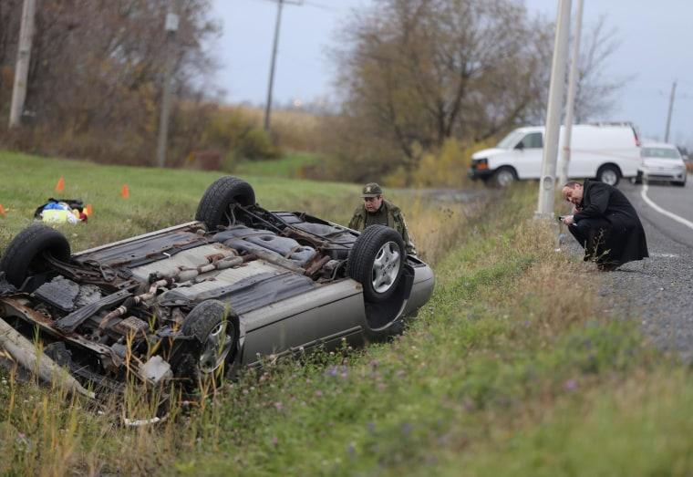 Image: Officer investigates an overturned vehicle