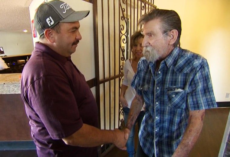 Image: Thomas Artiaga shakes hands with Robert Wells, whom he rescued from a fire