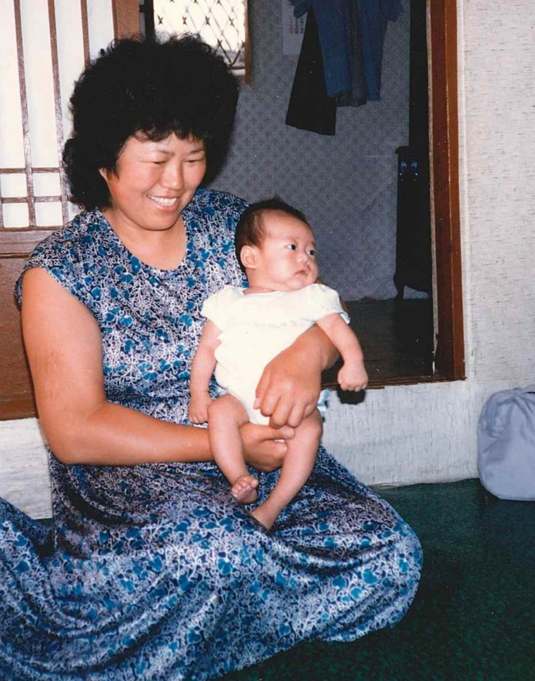 Image: Benjamin Oser as baby, held by Asian women in blue dress - Adoption Agency Caregiver, mid-summer 1984.