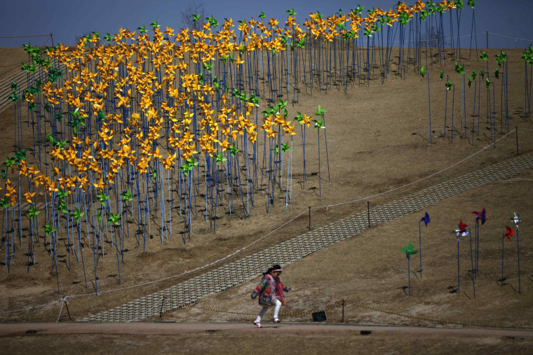 Image: A girl runs past pinwheels arranged in the shape of the Korean peninsula at Imjingak pavillion near the DMZ in Paju