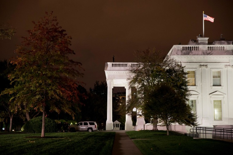 Image: A group of Secret Service police gather on the North Lawn as a member of the Secret Service Counter Assault team surveys from the White House rooftop