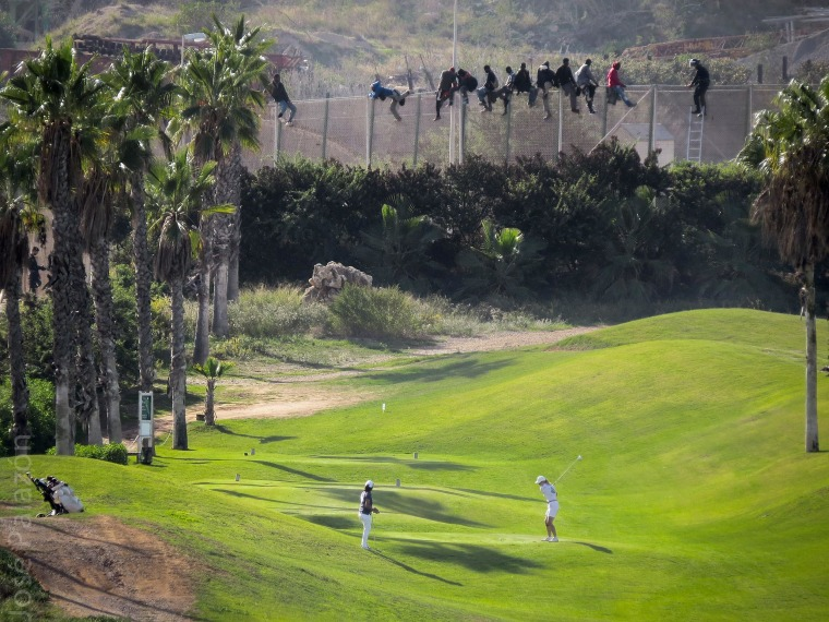 Image: Golfers playing from a fairway back-dropped by African migrants