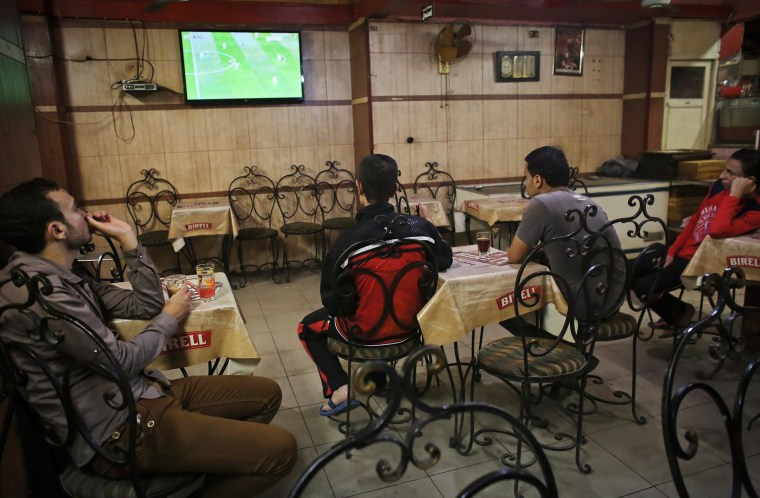 Image: Egyptian men watch a football match at a coffee shop in the city of Assuit