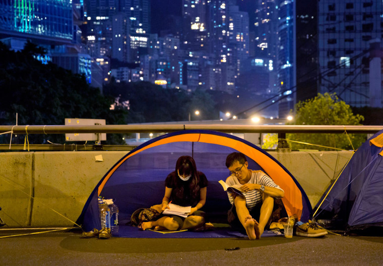 Image: A couple read inside their tent at the occupied area in Central, Hong Kong