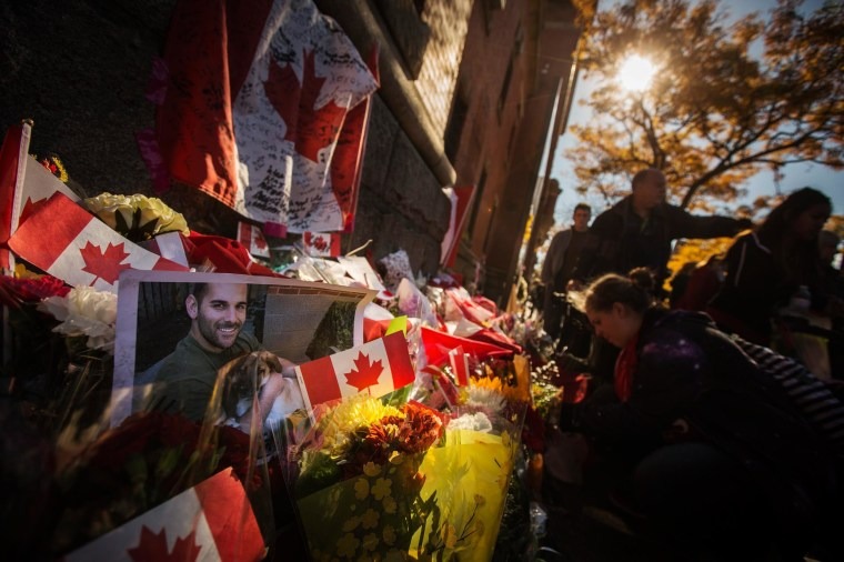 Image: A photograph of Cpl. Nathan Cirillo is displayed at a makeshift memorial in honour of his death, as people pay their respects in Hamilton