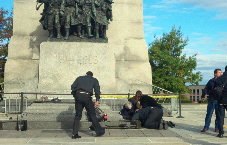Image: A Canadian soldier who was shot outside the war memorial on Parliament Hill in tended to in Ottawa