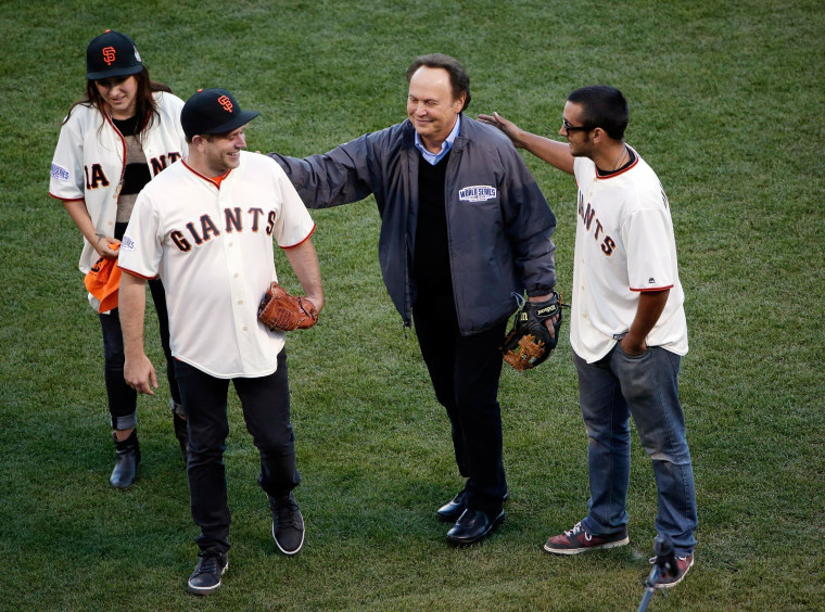 Image: Robin Williams son, Zak Williams, second from left, gets a pat on the back from Billy Crystal after Zak threw out the ceremonial first pitch