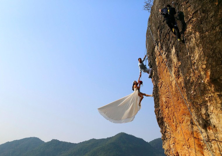 Image: Zheng Feng, an amateur climber takes wedding pictures with his bride on a cliff in Jinhua