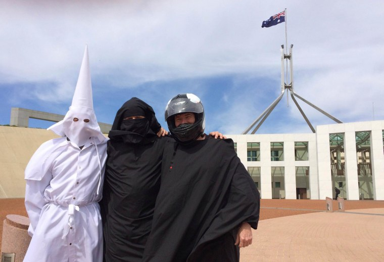 Image: Three men wearing a Ku Klux Klan hood, a niqab and a motorcycle helmet pose for a photo outside Australia's Parliament House in Canberra