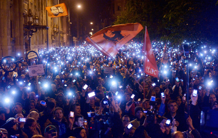 Image: Thousands of demonstrators light up their mobile phones as they march across the River Danube