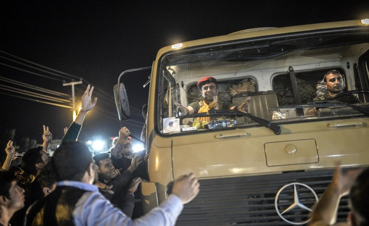 Image: A peshmerga fighter sitting in a truck gestures as Kurds in Turkey greet peshmerga convoys in Viransehir, in Turkey's southeastern Sanliurfa province