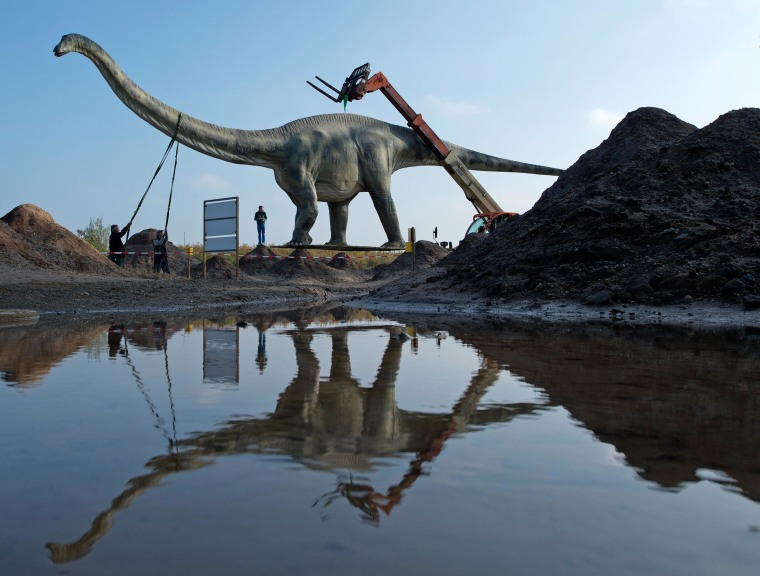 Image: Workers transport a model of a dinosaur