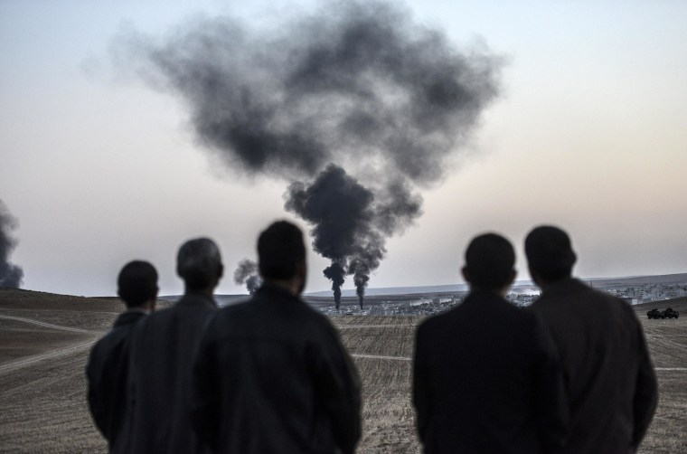 Image: People watch from the Turkish border as smokes rises from the Syrian town of Kobani.