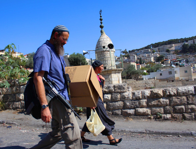 An armed Jewish settler and his wife walk in the neighborhood of Silwan in East Jerusalem.