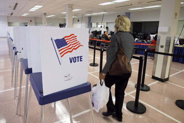 A woman walks past voting booths at the Cuyahoga County Board of Elections in Cleveland, Tuesday, Oct. 7, 2014. Early voting began in Ohio after the U.S. Supreme Court stepped into a dispute over the schedule, pushing the start date back a week in the swing state. (AP Photo/Mark Duncan)