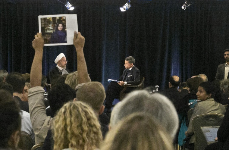 A protester holds up a picture of Ghoncheh Ghavami as Iran's President Dr. Hassan Rouhani, left, speaks with moderator Fareed Zakaria at New America, a public policy institute and think tank in New York on Wednesday, Sept. 24, 2014. Ghavami, a 25-year-old British-Iranian citizen, was among 50 women arrested in June for trying to watch a volleyball match from inside a stadium. (AP Photo/Bebeto Matthews)