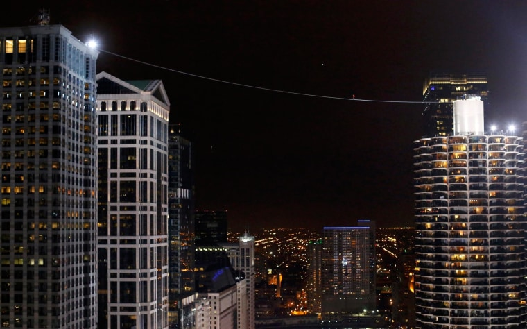 Image: Daredevil Nik Wallenda walks along a tightrope between two skyscrapers suspended 500 feet above the Chicago River