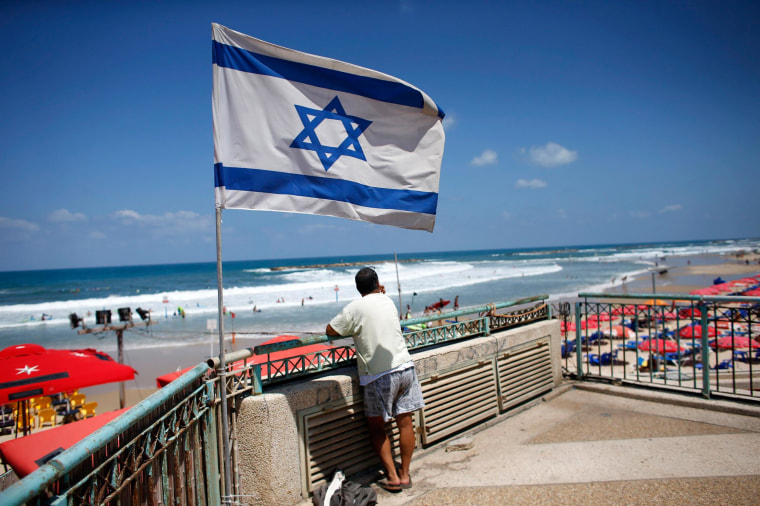 Image: A man looks at the sea as an Israeli flag flutters nearby in Tel Aviv
