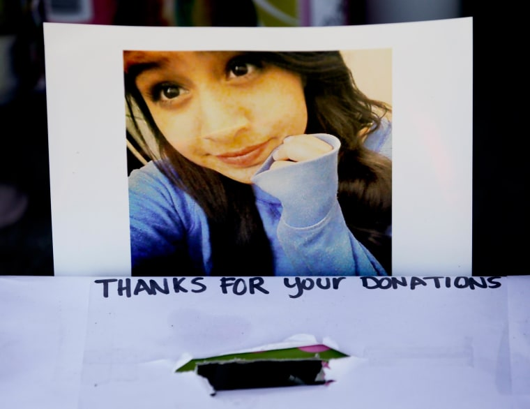 Image: A photograph of Andrea Gonzales is taped to a donation box at a makeshift memorial near where Gonzales and two other girls were killed