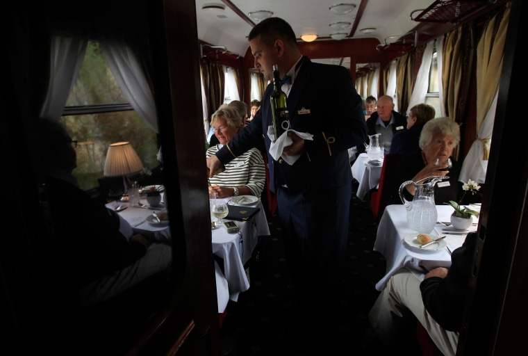 Image: Lunch is served aboard a historic Tehran-bound train as it leaves Budapest