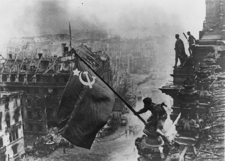 Russian soldiers fly the revolutionary Russian red flag over the ruins of the Reichstag in Berlin