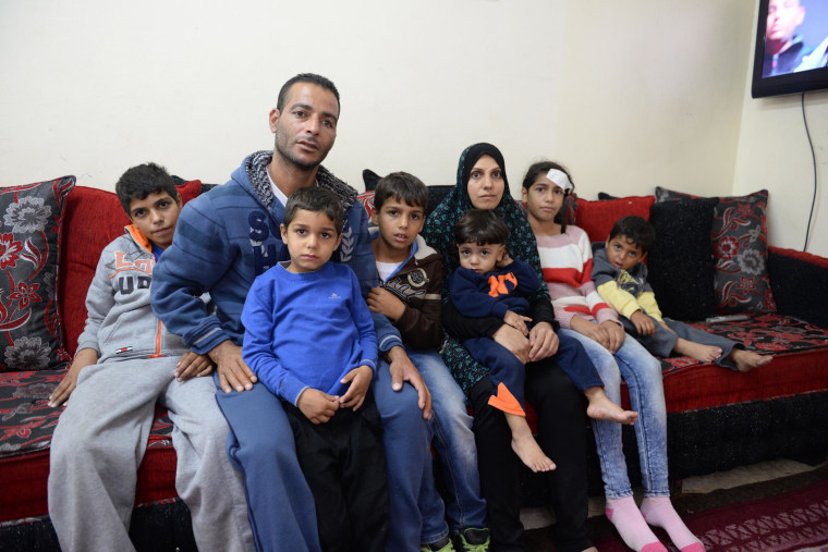 Fatimah Kayed Al-Rajabi, second right, sits with her parents and siblings inside their house in Silwan.