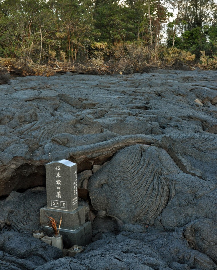 This Oct. 28, 2014, photo provided by the U.S. Geological Survey on Nov. 3, with the permission of the Sato family, shows the Sato headstone still standing in a sea of black lava in a cemetery in Pahoa, Hawaii.