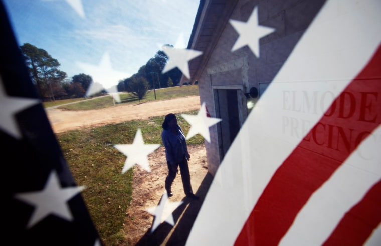 Image: Barbara Hawkins is seen through an American flag as she walks into the Elmodel precinct to cast her ballot