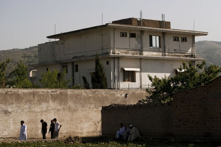 Image: People walk past Osama Bin Laden's compound in Abottabad, Pakistan, in 2011.