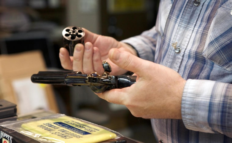 Image: A man inspects a revolver
