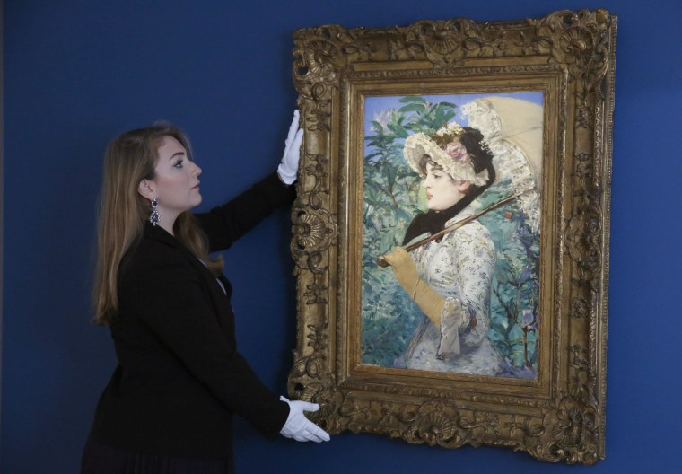 Image: A Christie's employee poses with painting by Manet