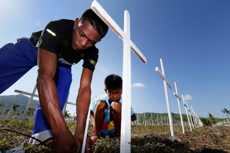 Twelve-year-old typhoon survivor Joshua Cator and his father Sulpicio Cator, Jr. offer candles at the grave site of Joshua's mother and sister at a cemetery for 3,000 typhoon victims in Tacloban City, Philippines, Nov. 7, 2014.