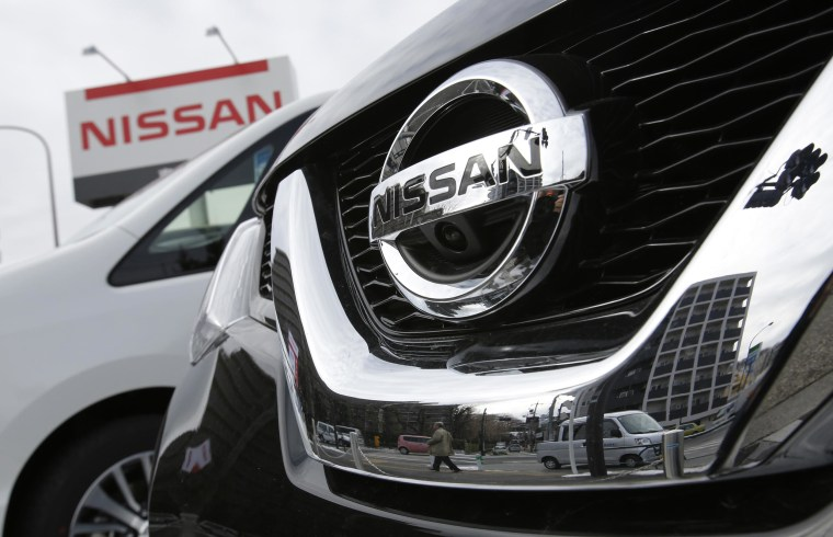 A pedestrian is reflected in a Nissan Motor car at the company's dealership in Tokyo